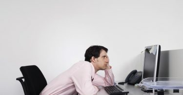 side-view-of-a-bored-male-office-worker-looking-at-notes-on-computer-monitor-at-desk