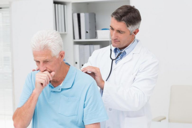 An old man is coughing as the doctor examines him