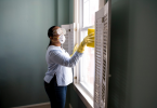 woman cleaning and disinfecting home while wearing protective equipment