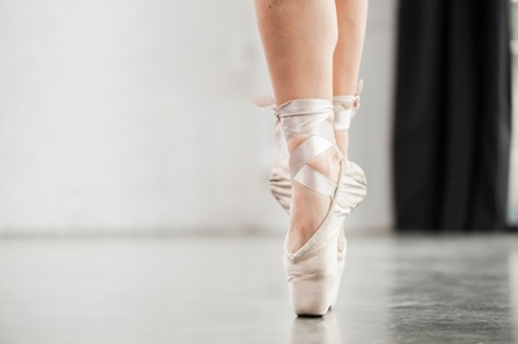 A ballerina's pointe shoes on the floor