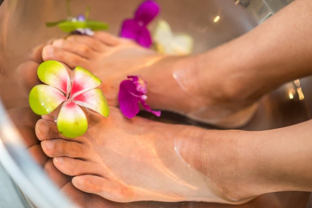 A person's feet soaked in a bowl full of water with flowers