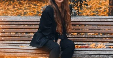 A girl in black women's wear resting on a bench in the fall