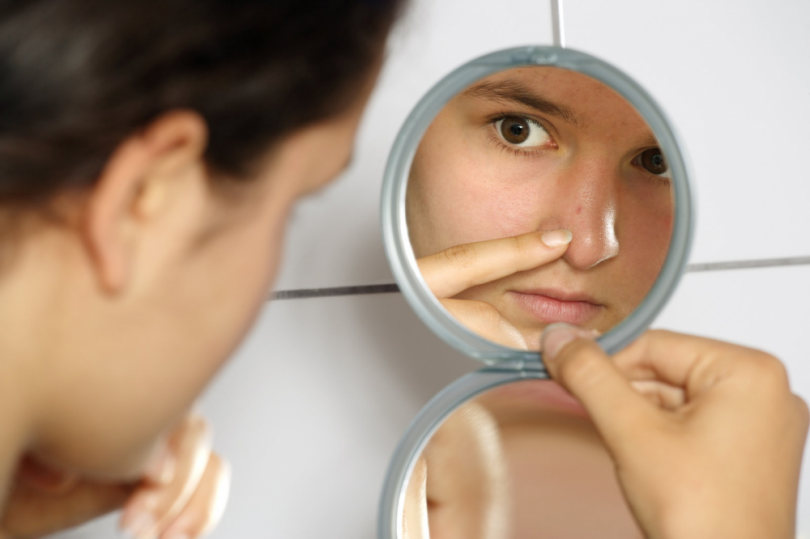 Young woman looking at herself in the mirror.