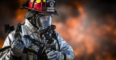 A firefighter in a protective suit with a gas mask putting out a bush fire
