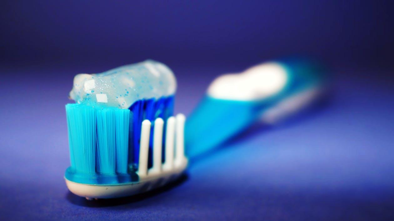 Toothpaste on a blue and white bristle toothbrush