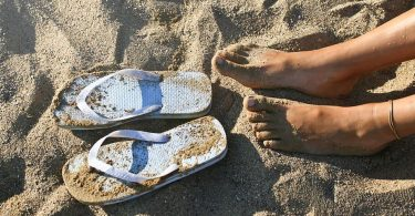 Woman's feet with flip flops on the sand.