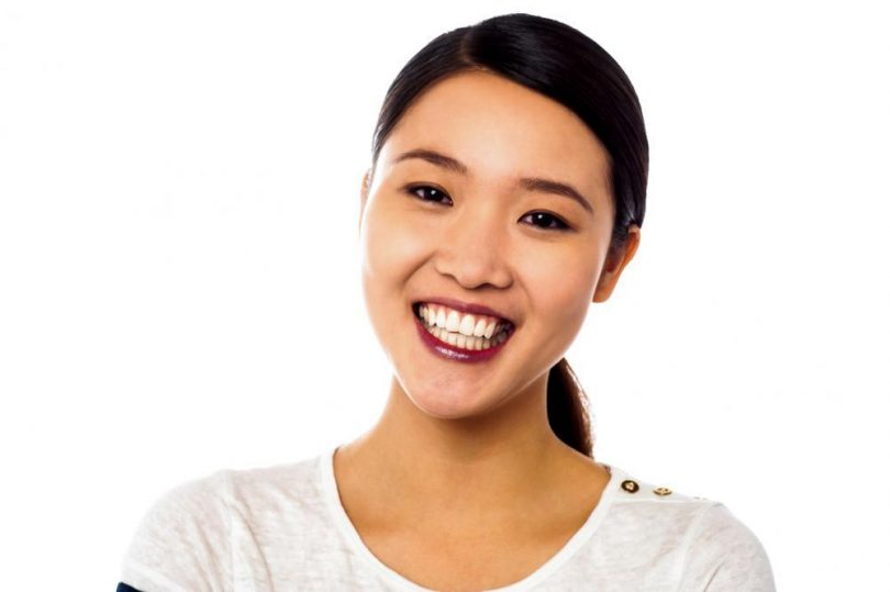 A woman smiling, showing her shiny clean teeth.