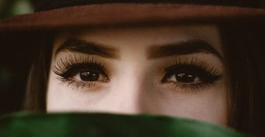 woman in a hat with long lash extensions