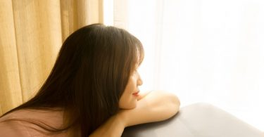 Asian woman resting her head on a sofa