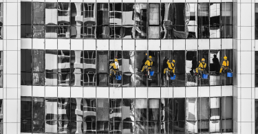 Five professional cleaners are cleaning a glass building