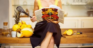 woman sitting on the counter with a book