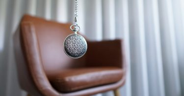 A silver pocket watch on a chain in front of a comfy chair depicting a hypnosis session