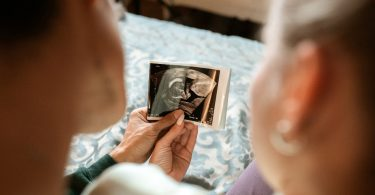 A couple looking at an ultrasound photo of their baby