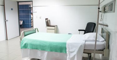 A vacant hospital room with a bed and chair