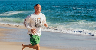 : A Man in Green Shorts and A White Shirt Running Barefoot Along the Beach