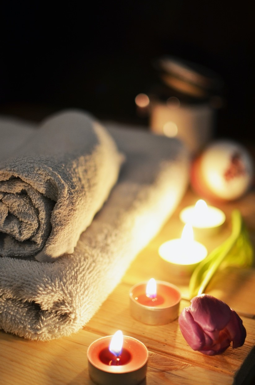 Towels, scented candles, and a rose in a spa