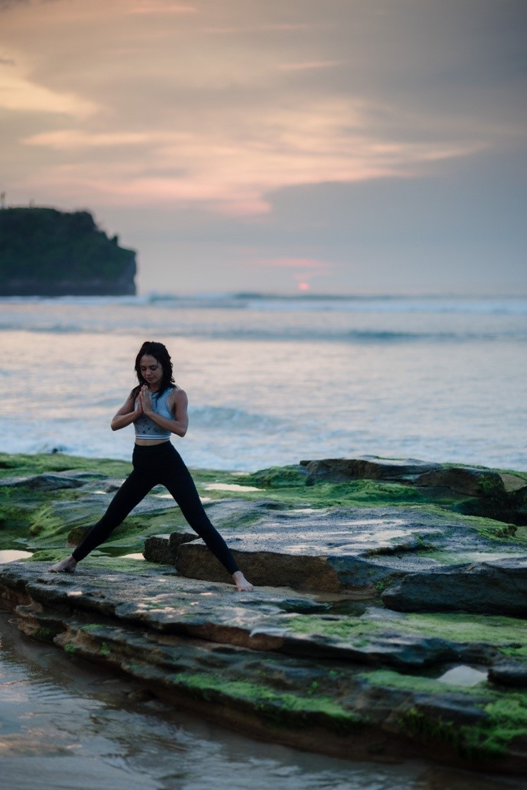 A person practicing a yoga pose near the ocean