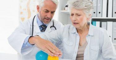 A doctor helping a senior use a stress ball