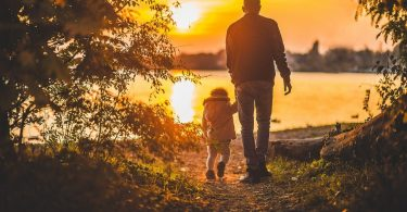 A father and a child by the lake