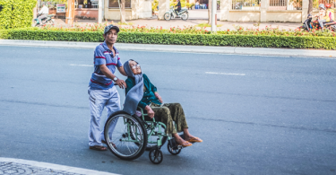 a person offering senior citizen care services to an old woman