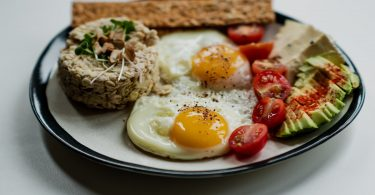 A Plate Containing Fried Eggs, Sunny-Side-Up, with Granola, Bread, Cherry Tomatoes, and Avocado
