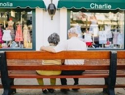 Old couple sitting on wooden bench.