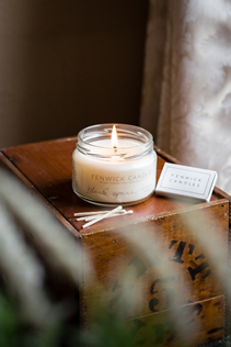 A lit candle on a bedside table
