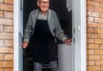 A senior citizen standing at the door