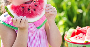 A Little Girl Biting into a Watermelon Slice