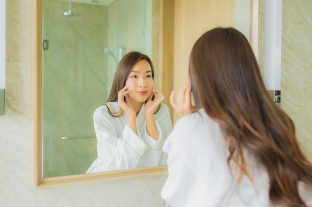 a woman looking in the mirror post-microdermabrasion
