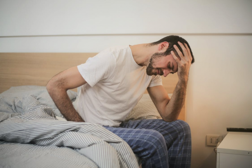 A man hunched in pain and discomfort as he sits awake in bed.