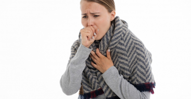 woman holding chest while coughing