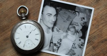 A black and white photo of a baby and father, lying next to an old stopwatch