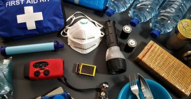 First aid and survival kit spread out on flat surface