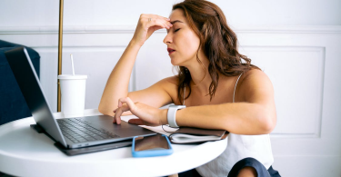 A Woman Sitting in Front of Her Laptop and Pinching Her Forehead in Visible Distress