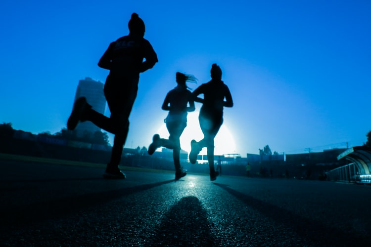 A group of runners out for a jog on a road.