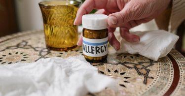 a patient holding a prescribed allergy medicine bottle