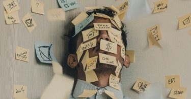 A stressed man covered in sticky notes