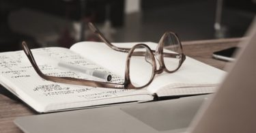 A pair of glasses and a pen lying on a notebook