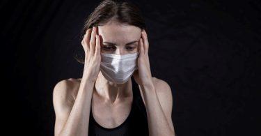 A woman needing mental health help holding her head